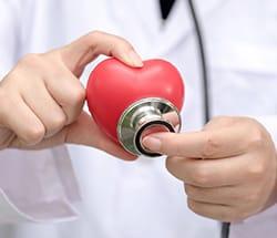 lekarz trzymający w dłoniach atrapę serca