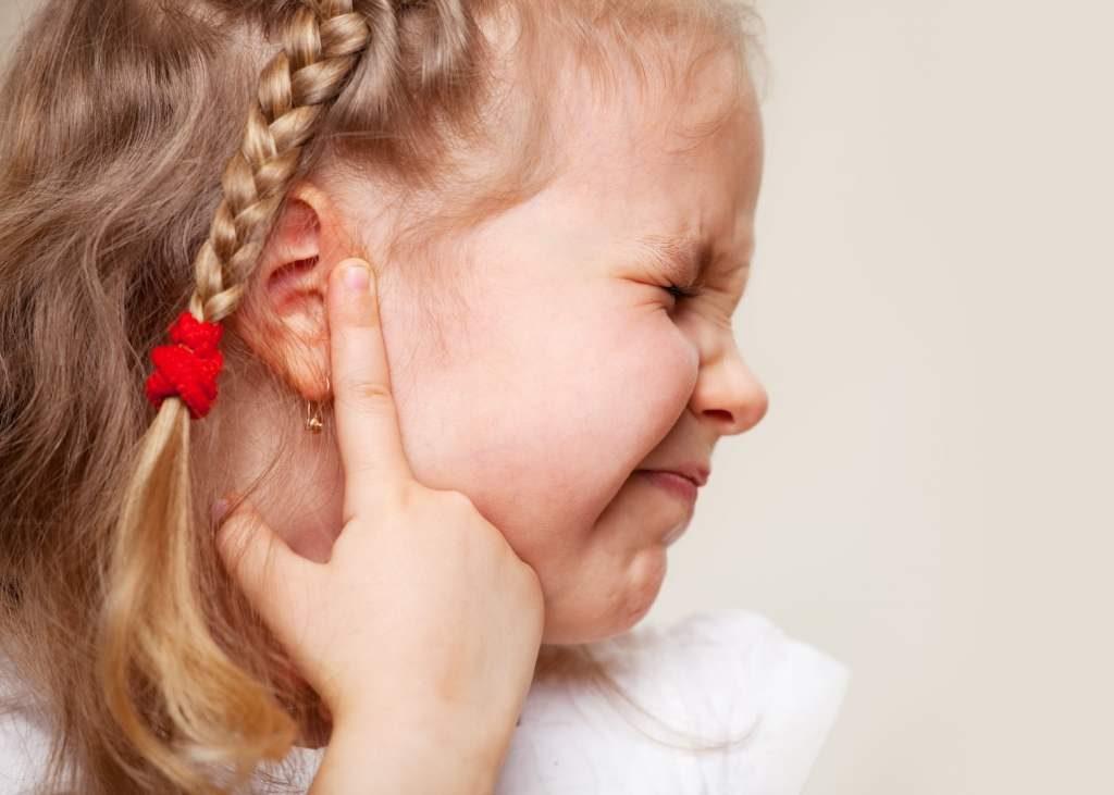 mała dziewczynka wskazująca palcem na bolące ucho