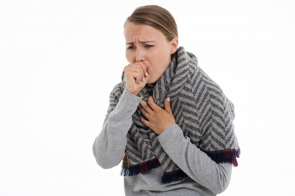 kobieta z powikłaniami grypowymi, trzyma ręką bolącą klatkę piersiową