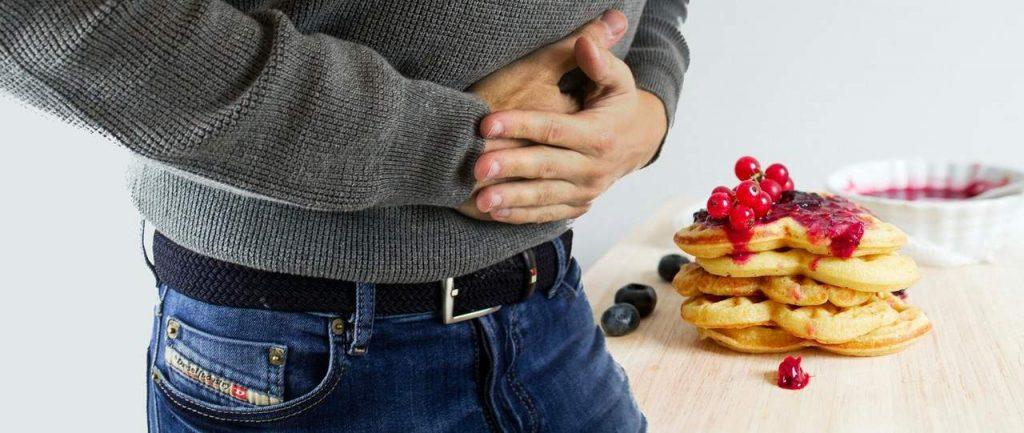 mężczyzna, który trzyma się za bolący żołądek