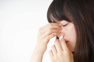 kobieta tamująca wyciek wydzieliny z nosa