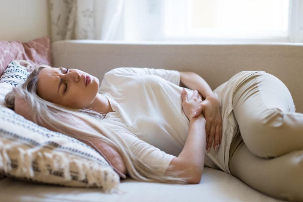 kobieta leżąca na łóżku, cierpiąca na ból brzucha wywołany chorobą Whipple'a