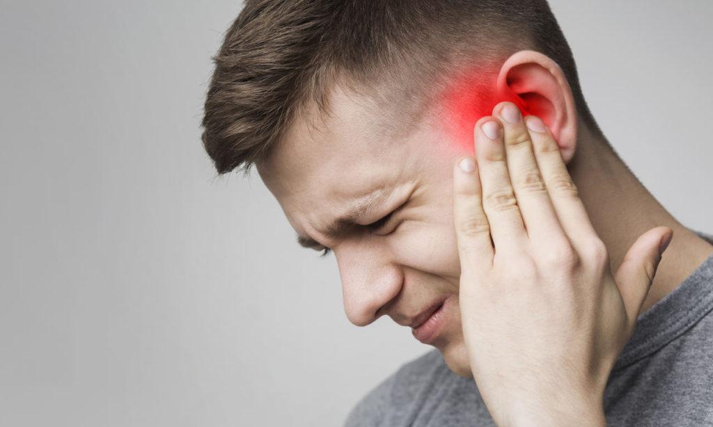 mężczyzna cierpiący na zapalenie nerwu przedsionkowo-ślimakowego trzyma się za bolące ucho