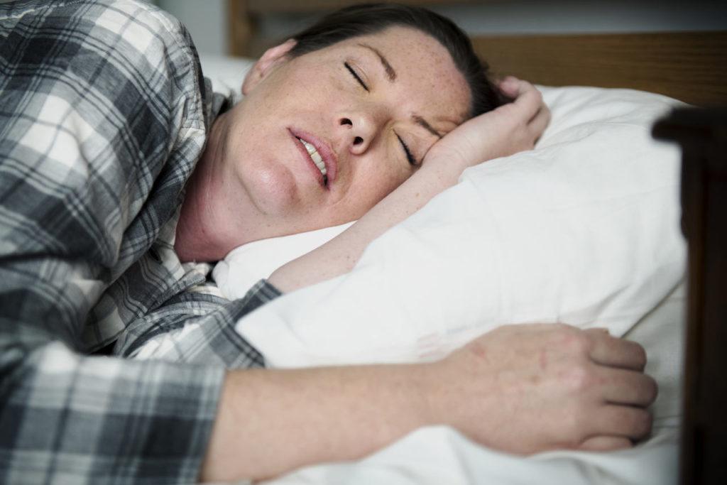 śpiąca kobieta, u której podczas snu występuje bezdech senny