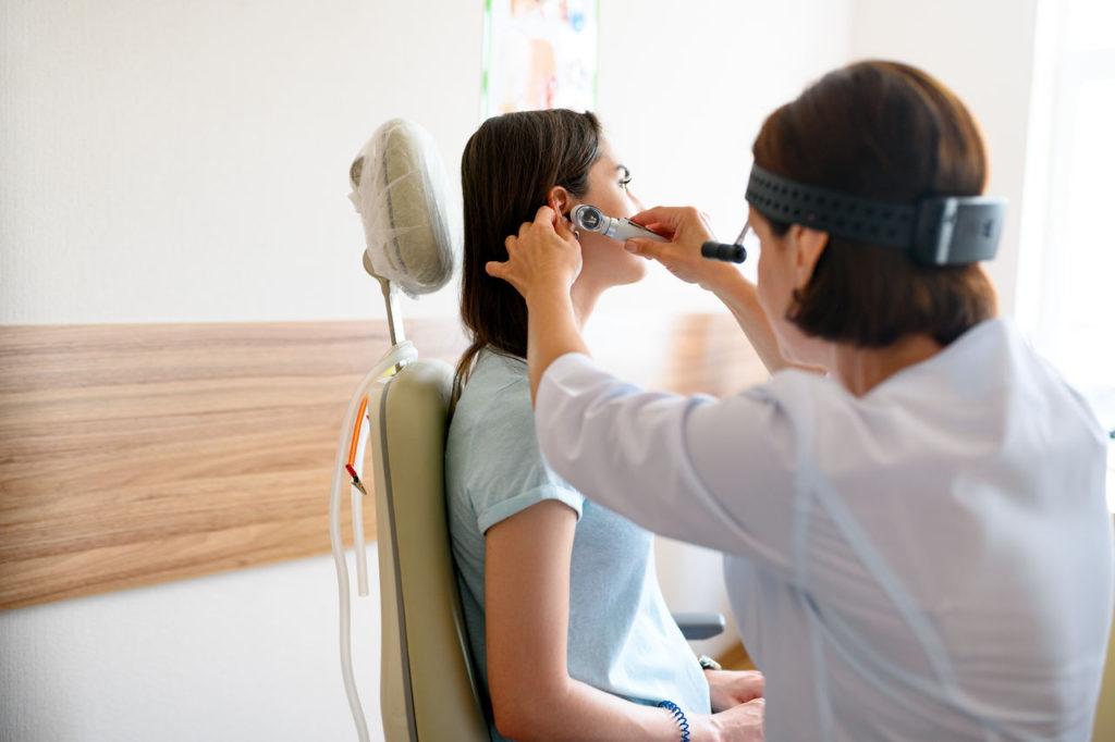 laryngolog bada pacjentkę cierpiącą na powikłania po zapaleniu ucha środkowego