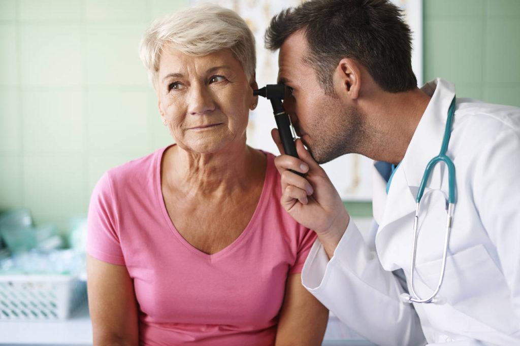 laryngolog bada kobietę skarżącą się na zatkane ucho