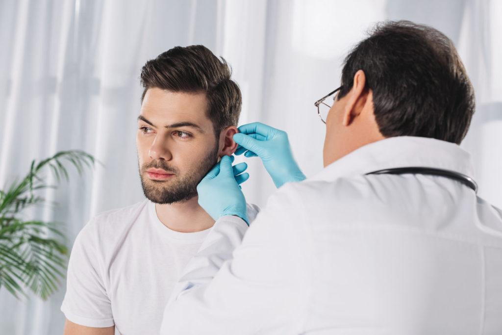 laryngolog bada mężczyznę cierpiącego na zapalenie wyrostka sutkowatego