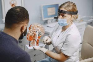 laryngolog objaśnia pacjentowi mikrolaryngoskopię krtani