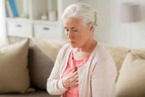 starsza kobieta trzyma rękę na sercu, ponieważ odczuwa kołatanie serca