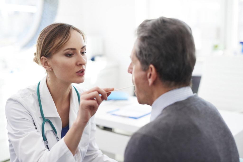 laryngolog bada pacjenta z podejrzeniem leukoplakii