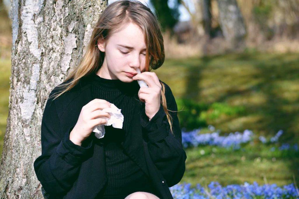 dziewczyna zmagająca się z alergią krzyżową stosuje leki na alergię