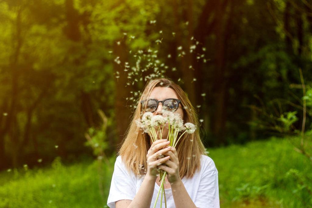 kobieta dmucha w dmuchawce latem i zmaga się z letnią alergią