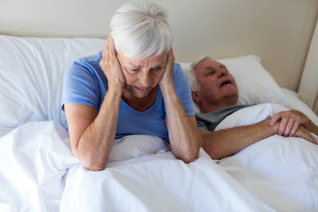 kobieta zatyka uszy ponieważ jej starszy mąż chrapie