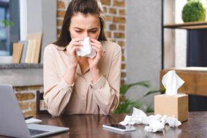 kobieta zmagająca się z alergią na kurz wyciera nos za pomocą chusteczek