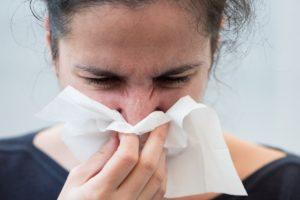 kobieta cierpiąca na katar sienny, wyciera nos chusteczką